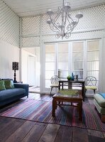 Metal chandelier above carved wooden coffee table on striped rug in foyer with white wooden latticed walls