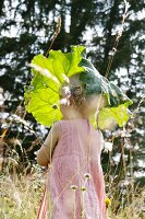 Blond girl holding rhubarb leaf as parasol