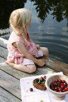 Little blond girl with cherries by the side of a pond