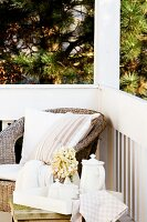 Wicker chair with cushions and tea service on side table in corner of rustic veranda
