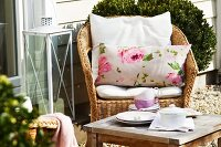 Tea break in garden - wicker chair with cushions and cups on rustic side table in front of house