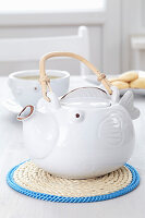 Fish-shaped teapot on handmade twine mat