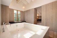blaugraue treppenstufen an freistehender badewanne vor wand mit mosaikfliesen im retrostil. Black Bedroom Furniture Sets. Home Design Ideas