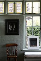 Still-life of framed pictures and simple country-house chair in front of lattice window, stained leaded glass and whitewashed brick wall. Upholstered window seat invites you to linger.