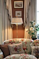 Cushions on rose-patterned sofa in front of illuminated, antique-style standard lamp between elegant curtains and against russet-painted wall with framed landscapes
