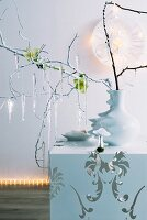 Artistic Christmas atmosphere - glass icicles hanging from twigs in white china vase on cubic side table against wall lit with fairy lights