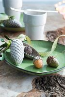 Acorns and fir cones on dish in front of white china beaker and fork on rustic wooden surface