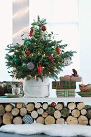 Decorated Christmas tree and presents on white shelf resting on stacked logs