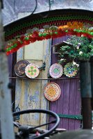 View through vehicle windscreen of round chopping boards painted with colourful patterns leaning on purple painted wooden door