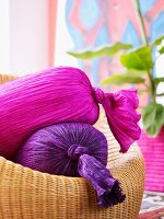 Two crushed silk bolsters in magenta and purple on wicker sofa