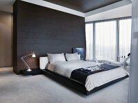 frühstückstablett auf doppelbett vor schwarz gefliestem raumteiler ... - Schlafzimmer Mit Raumteiler