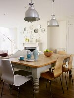 Rustic kitchen table and modern chairs below industrial lamps in country-style interior