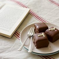 Petits fours next to cake forks on plate and open book on linen tablecloth