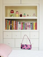 Bed in front of fitted cabinet with shelves and handbag hanging from drawer handle