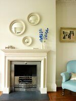 Open fireplace with traditional mantel and circular, framed mirrors on wall
