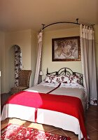 Red and white bedroom with wrought iron bed and curtains (Villa Octavius, Lefkas, Greece)