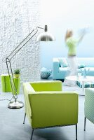 Interior in shades of aquamarine with green armchair & stainless lamp