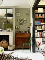 Corner of traditional living room with antique bureau next to open fireplace and view of armchair in front of bookcase through wide doorway