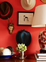 Posy in metal beaker flanked by table lamp and dish of ornamental fruit below collection of hats hanging on red-painted wall