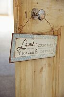 Door sign hanging on knob of rustic, interior wooden door