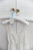 Dress with spaghetti straps on clothes hanger hanging on wardrobe door