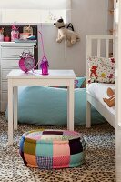 White table next to white bed and pouffe in child's bedroom