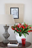 Tulips in white vase next to bedside lamp