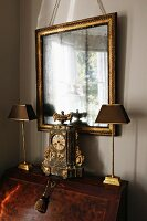 Antique clock flanked by lamps on top of bureau below gilt-framed mirror on wall