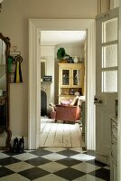 Open front door in hallway with chequered tiles on floor and view into comfortable living room with vintage-style white floorboards and dresser