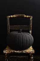 A Large Pumpkin, Painted Black, on an Old Chair