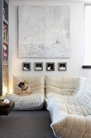White seating area with comfortable corner couch below white, abstract painting