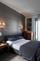 Grey upholstered bed and antique wooden furniture against monochrome striped wallpaper