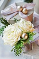 Christmas posy of white roses next to gift box