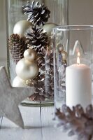 Arrangement of white pillar candle in lantern and Christmas decorations in glass jar
