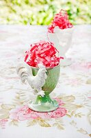 Outside -- egg cups filled with pink Easter grass on a rose patterned tablecloth