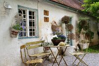 Rustic garden table and chairs on gravel floor in front of bungalow