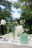 Delicate summer flowers in small glass vases and turquoise china jug on white wooden table