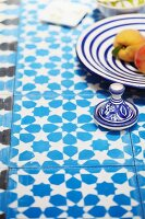 Blue and white crockery on blue and white tiled table top with floral pattern