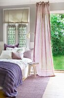 Comfortable bed with purple throw next to fluttering, mauve curtain in front of open door leading to garden