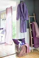 Open garden door with fluttering curtain in sunny room with lilac and violet accents