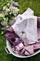 View of rustic zinc tub with purple textiles, scented soap, perfume and shower gel