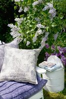 Lilac cushions on garden chair next to flowering lilac