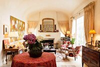 Hydrangea plant on a round table in sitting room with coved ceiling and fabric by Kathryn Ireland