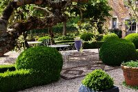 Garden table and chairs on gravel amongst topiary bushes and hedges