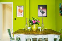Candlestick and bouquet on antique table below modern, framed posters on green wall