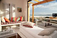 Living room and terrace with an ocean view - cozy upholstered day beds by an open picture window in front of a terrace
