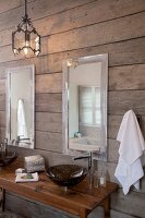 Dark, wash basin on a wooden table with designer fittings and mirrors on a rustic, wood plank wall