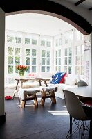Sheepskins on cosy corner bench, wooden table and stools in conservatory with lattice windows