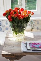 Glass vase of orange and red tulips on rustic wooden table