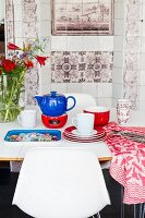 Tea set on dining table in front of traditional tiled stove